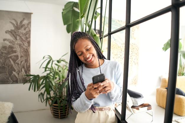휴대 전화를 사용하여 그녀의 스마트 폰 웃는 소녀에 채팅 젊은 아프리카 계 미국인 여자