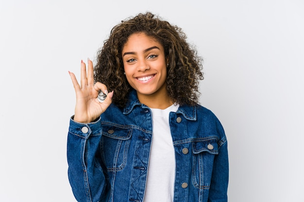 Young african american woman cheerful and confident showing ok gesture.