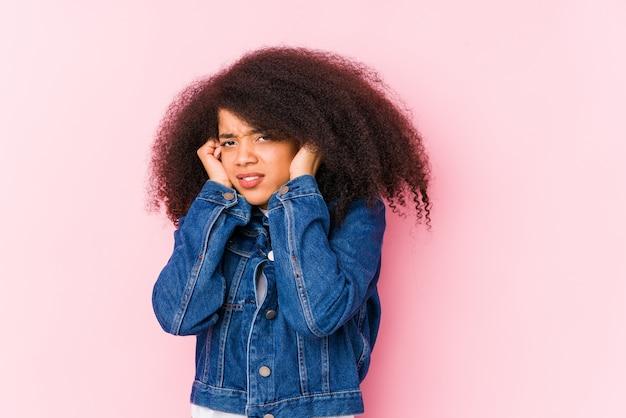 손으로 귀를 덮고 젊은 아프리카 계 미국인 여자.