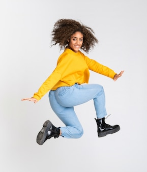 Young african american woman dancing over isolated white