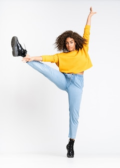 Young african american woman dancing on isolated white