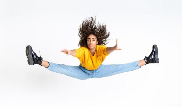 Молодая афро-американская женщина танцуя над изолированным белым пространством