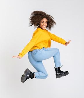 Молодая афро-американская женщина танцуя над изолированной белизной
