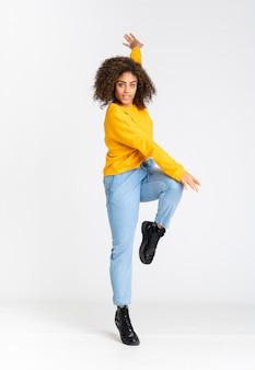 Молодая афро-американская женщина танцует над белой стеной