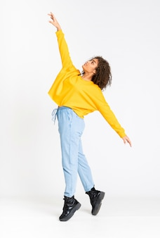 Young african american woman dancing over white wall