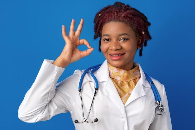 Молодая афро-американская женщина-врач показывает знак ок на синем фоне