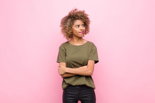 若いアフリカ系アメリカ人女性の疑いや思考、唇をかむと不安と緊張を感じて、ピンクの壁に対して側のスペースをコピーしよう