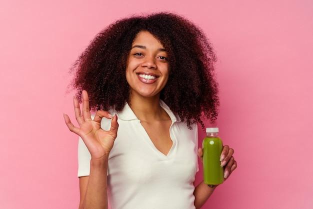 ピンクの背景に分離された健康的なスムージーを飲んでいる若いアフリカ系アメリカ人の女性は、明るく自信を持って大丈夫なジェスチャーを示しています。