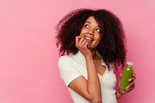ピンクの背景に分離された健康的なスムージーを飲む若いアフリカ系アメリカ人の女性は、コピースペースを見ている何かについて考えてリラックスしました。