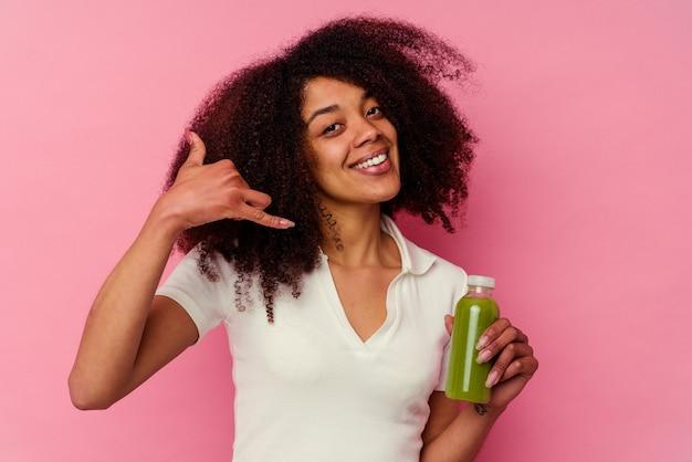 指で携帯電話の呼び出しジェスチャーを示すピンクの背景に分離された健康的なスムージーを飲む若いアフリカ系アメリカ人の女性。