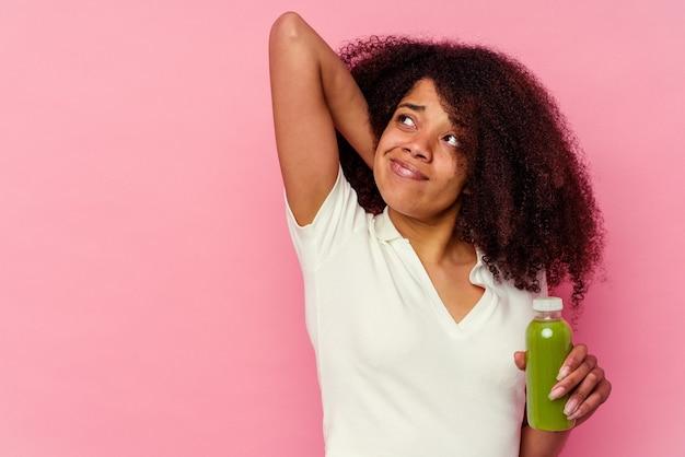 Молодая афро-американская женщина пьет здоровый коктейль на розовом фоне, касаясь затылка, думая и делая выбор.