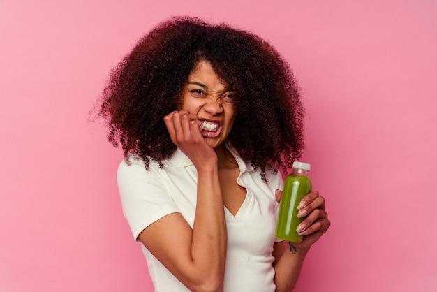 ピンクの噛む指の爪で隔離された健康的なスムージーを飲んでいる若いアフリカ系アメリカ人の女性、神経質で非常に心配しています。