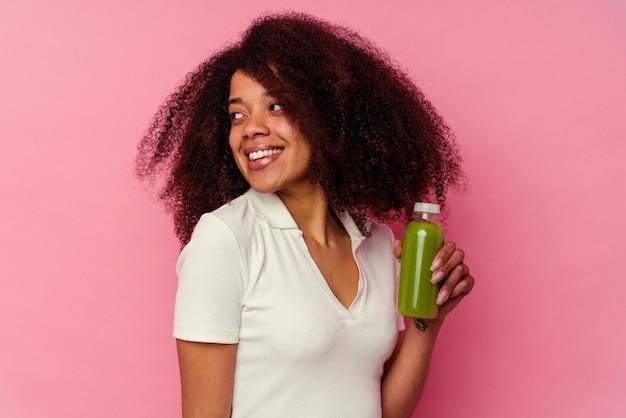 ピンクで隔離された健康的なスムージーを飲む若いアフリカ系アメリカ人の女性は、笑顔、陽気で楽しいことはさておきに見えます。