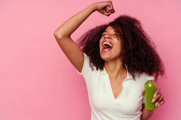 勝利、勝者の概念の後にピンクのくいしばられた握りこぶしで隔離される健康的なスムージーを飲む若いアフリカ系アメリカ人の女性。