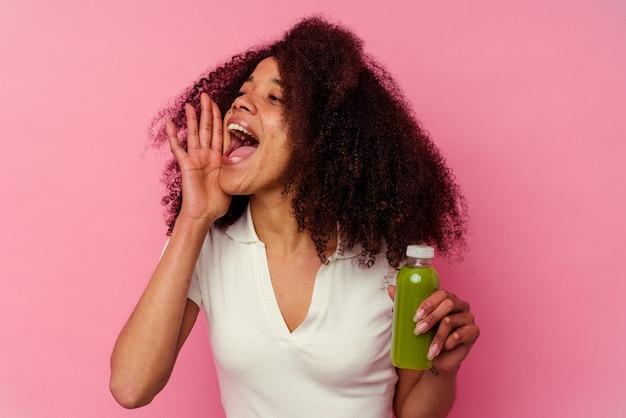 ピンクの叫びで隔離された健康的なスムージーを飲み、開いた口の近くで手のひらを保持している若いアフリカ系アメリカ人の女性。