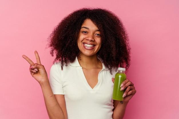 ピンクで隔離された健康的なスムージーを飲んでいる若いアフリカ系アメリカ人の女性は、指で2番目を示しています。
