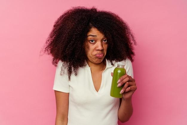 ピンクの肩をすくめ、目を開けて孤立した健康的なスムージーを飲む若いアフリカ系アメリカ人の女性は混乱しています。