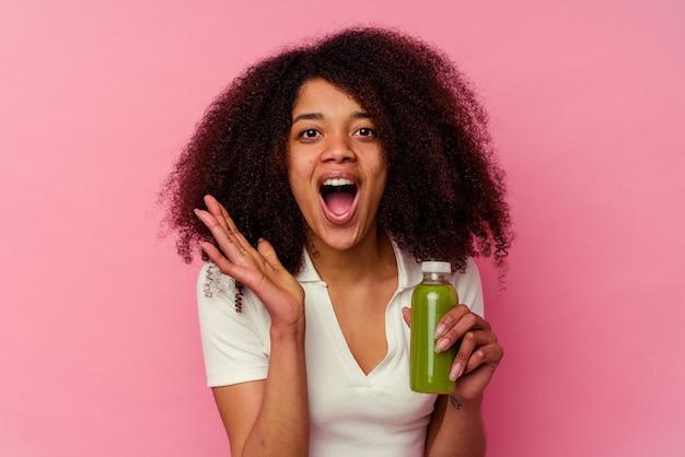 ピンクで隔離の健康的なスムージーを飲んでいる若いアフリカ系アメリカ人の女性は驚いてショックを受けました。