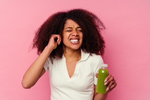 Young african american woman drinking a healthy smoothie isolated on pink background covering ears with hands.