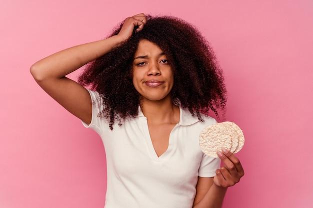 Молодая афро-американская женщина ест рисовые лепешки на розовом фоне в шоке, она вспомнила важную встречу.
