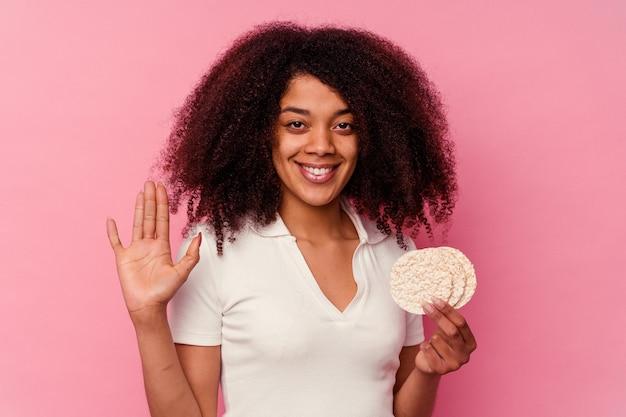 Молодая афро-американская женщина ест рисовые лепешки, изолированные на розовом фоне, улыбается веселый, показывая номер пять с пальцами.