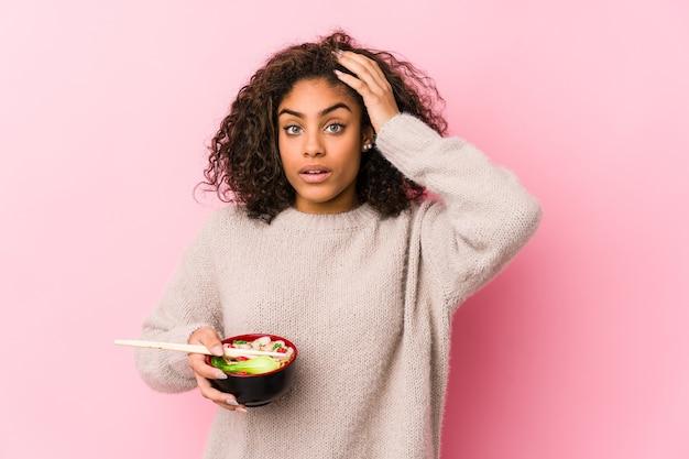 Молодая афро-американская женщина ест лапшу в шоке, она вспомнила важную встречу.