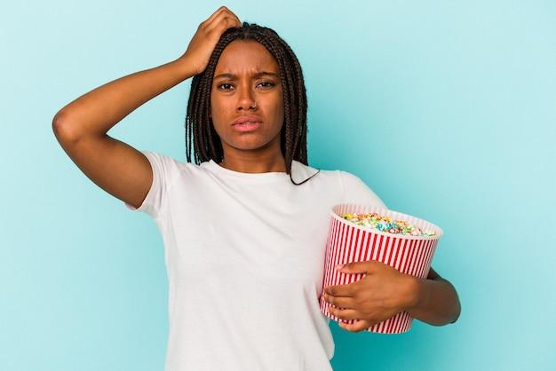 ショックを受けている青い背景に分離されたポップコーンを食べる若いアフリカ系アメリカ人の女性、彼女は重要な会議を思い出しました。