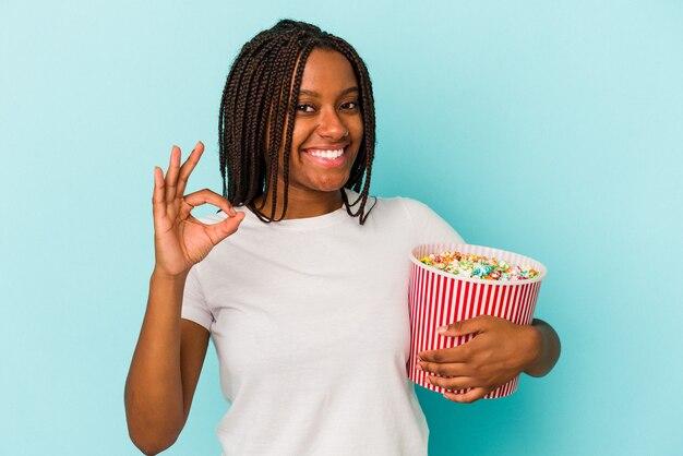 青の背景に分離されたポップコーンを食べる若いアフリカ系アメリカ人女性は、陽気で自信を持って大丈夫なジェスチャーを示しています。