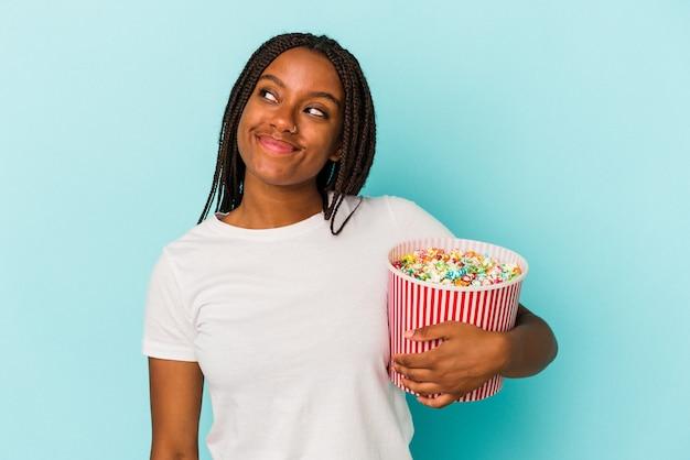目標と目的を達成することを夢見て青い背景に分離されたポップコーンを食べる若いアフリカ系アメリカ人女性