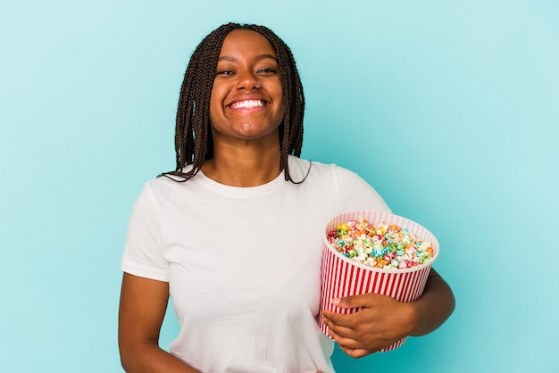 笑って楽しんで青い背景に分離されたポップコーンを食べる若いアフリカ系アメリカ人女性。