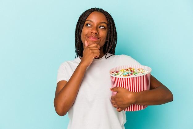疑わしいと懐疑的な表現で横向きに見える青い背景に分離されたポップコーンを食べる若いアフリカ系アメリカ人の女性。