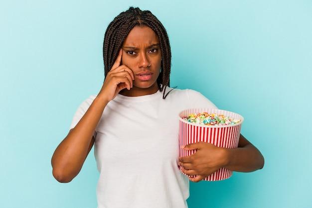 指で寺院を指し、考え、タスクに焦点を当て、青い背景で隔離のポップコーンを食べる若いアフリカ系アメリカ人の女性。