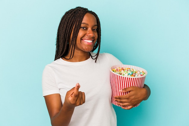 誘うようにあなたに指で指している青い背景に分離されたポップコーンを食べる若いアフリカ系アメリカ人の女性が近づいています。