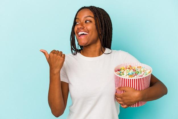 離れて親指の指で青い背景のポイントに分離されたポップコーンを食べて、笑ってのんきなアフリカ系アメリカ人の若い女性。