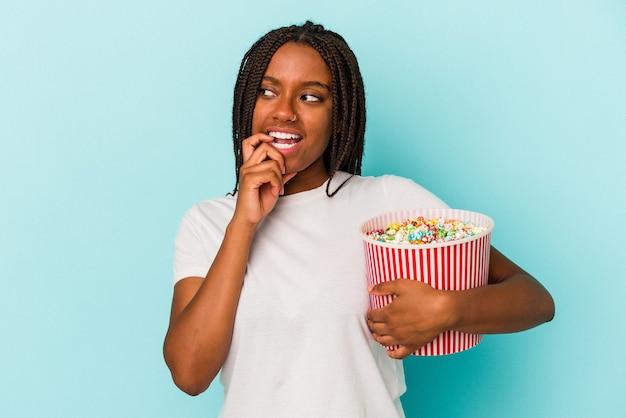 青い背景に分離されたポップコーンを食べる若いアフリカ系アメリカ人の女性は、コピースペースを見ている何かについて考えてリラックスしました。