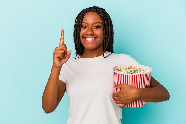 指でナンバーワンを示す青い背景に分離されたポップコーンを食べる若いアフリカ系アメリカ人女性。