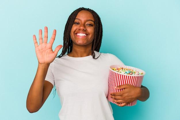 青い背景に分離されたポップコーンを食べる若いアフリカ系アメリカ人の女性は、指で5番目を示す陽気な笑顔を浮かべています。