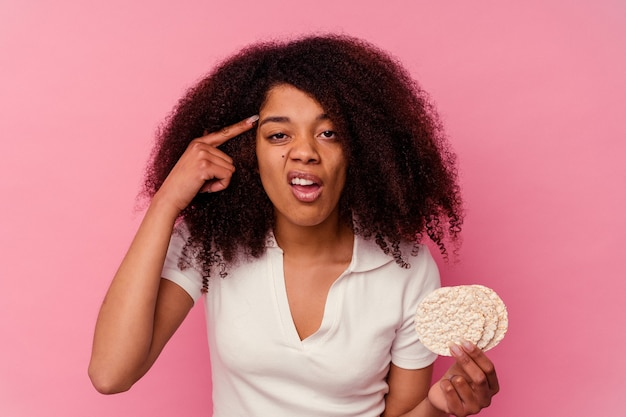 Young african american woman eating a rice cakes isolated on pink wall showing a disappointment gesture with forefinger.
