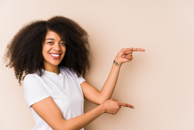 Young african american woman excited pointing with forefingers away.