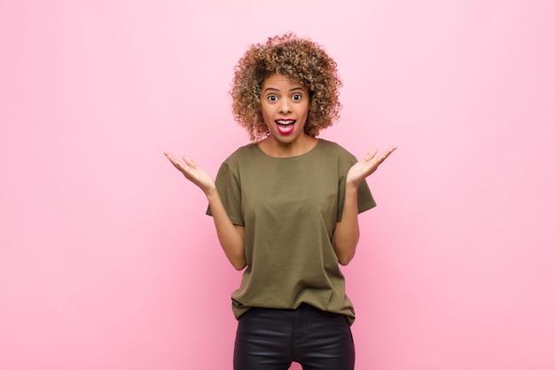 행복, 흥분, 놀라움 또는 충격을 느끼고 웃고 분홍색 벽에 믿을 수없는 것에 놀란 젊은 아프리카 계 미국인 여자