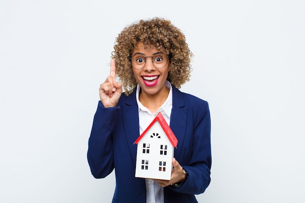 Young african american woman feeling like a happy and excited genius after realizing an idea, cheerfully raising finger, eureka! with house model