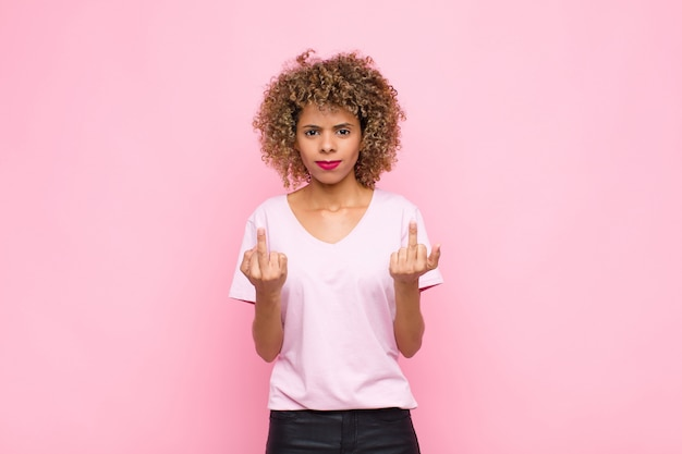 Young african american woman feeling provocative, aggressive and obscene, flipping the middle finger, with a rebellious attitude against pink wall