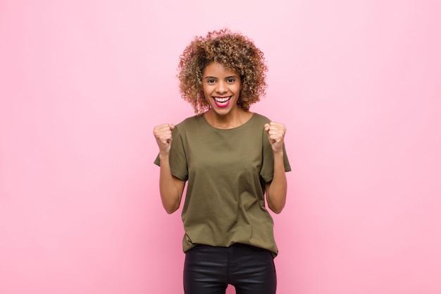 젊은 아프리카 계 미국인 여성은 충격을 받고 흥분하고 행복하며 웃고 성공을 축하하며 와우라고 말합니다! 분홍색 벽에
