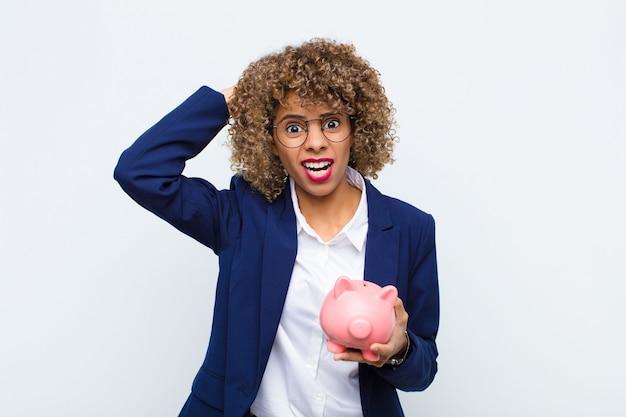 Молодая афроамериканская женщина, чувствуя стресс, беспокойство, тревогу или испуг, с руками на голове, паникует по ошибке с копилкой