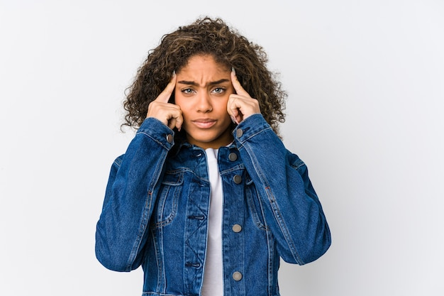 Молодая афро-американская женщина сосредоточилась на задаче, держа указательные пальцы, указывая головой.