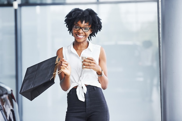 Young african american woman in glasses stands indoors with package in hands.