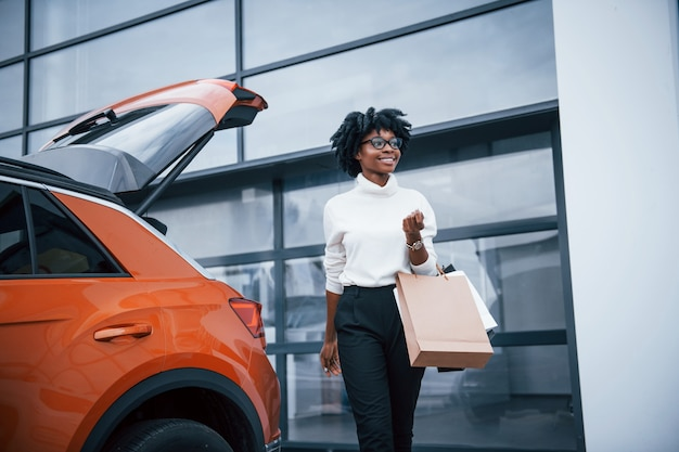 Young african american woman in glasses stands outdoors near modern car after shopping with packages.