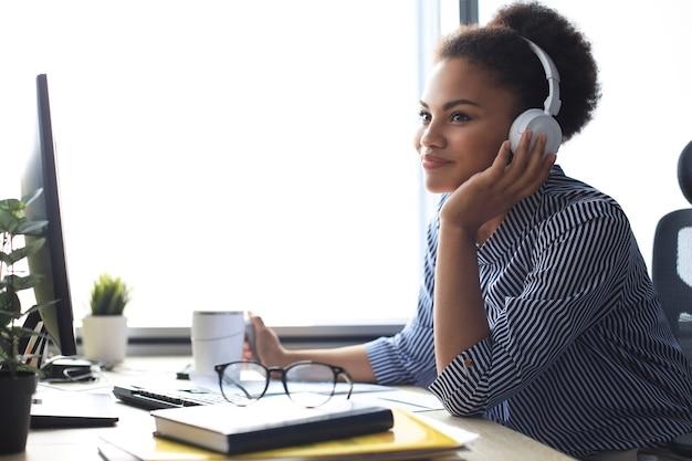休憩を取り、職場に座ってヘッドフォンで音楽を聴いている若いアフリカ系アメリカ人の女性。
