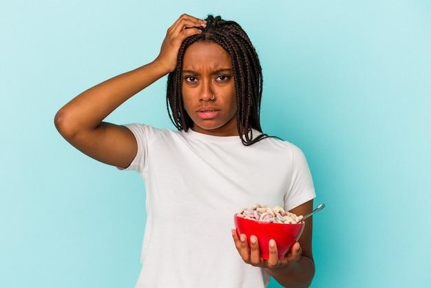 Молодая афро-американская женщина, держащая миску с хлопьями, изолированными на синем фоне, потрясена, она вспомнила важную встречу.