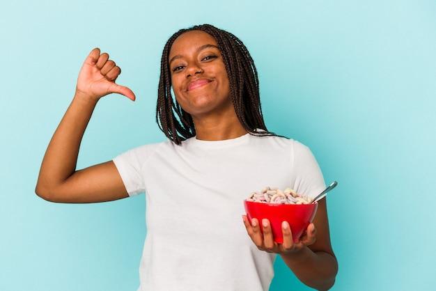 青い背景に隔離されたシリアルのボウルを保持している若いアフリカ系アメリカ人の女性は、誇りと自信を持って感じます。